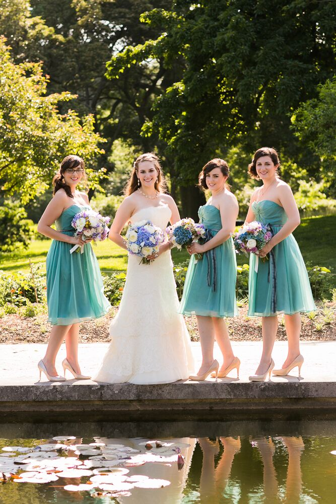 "Alexandra's bridesmaids wore knee-length, green chiffon dresses from Bella Bridesmaids. ""Initially I was going to let my bridesmaids choose their own style of dress in the same color and fabric, but in a happy accident, all three chose the same dress,"" Alexandra says."