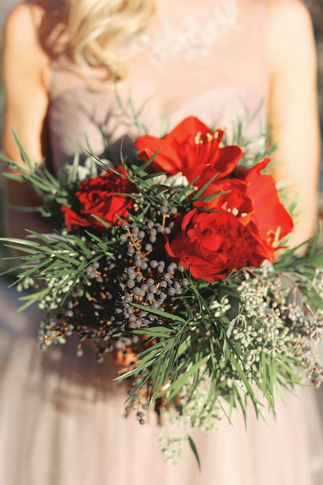 The bridesmaids' bouquets complemented the bride's with red amaryllis, berries and winter greenery.