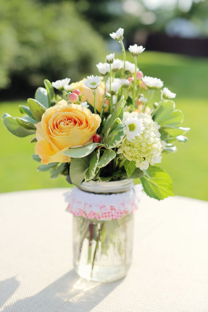 Peach roses mixed with a blend of white flowers in mason jars created simple, country-inspired centerpieces for the cocktail-hour tables.