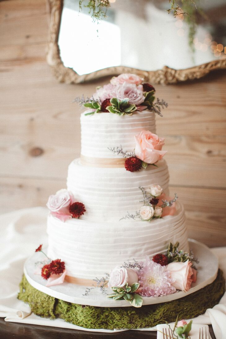 The couple chose a three-tier white wedding cake accented by champagne ribbon. Made by Alessi Bakery, the confection had oreo, hazelnut and lemon cake with berry preserves covered by textured buttercream frosting. Each tier was met with a fresh blush rose, blush dahlia and burgundy dahlia.