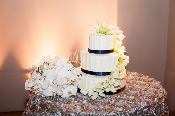 The three-tier white wedding cake had midnight blue ribbon wrapped around the bottom of each layer, filled with flavors of red velvet and vanilla bean. The cake had white orchids that started from the top and draped down to the bottom.