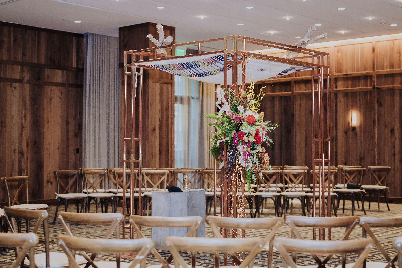Modern Gold Chuppah With Flower Arrangements In Hotel Ballroom
