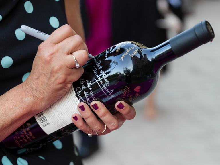 guest signing wine bottle