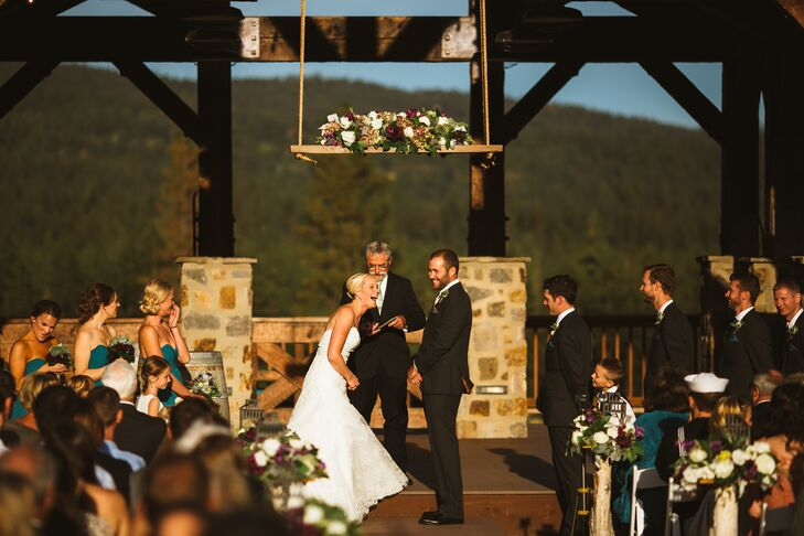 Bethany and Lucas got married in front of the elevated deck of a rustic structure on the venue's lawn, built with stone and wood. They stood under a hanging wooden beam topped with lush flowers.