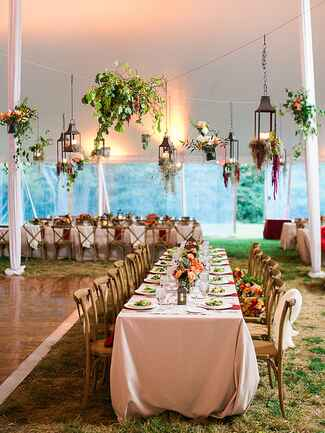 Outdoor tented wedding reception with hanging lanterns and greenery
