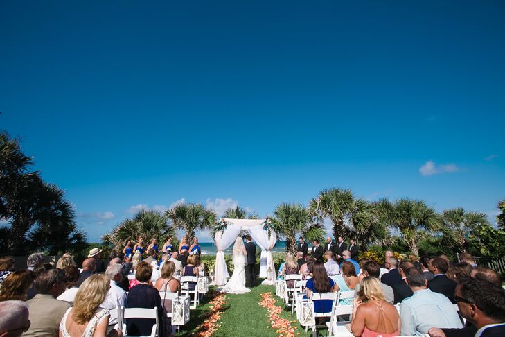 """We knew we wanted an outdoor venue overlooking the ocean, and this provided the perfect setting,"" Ashley says. Their planner from the Dtales helped decorate Ashley and Phil's ceremony at Hammock Beach Resort in Palm Coast, Florida, with all beach-inspired decor. Lanterns filled with sand and seashells marked the waterfront aisle while pink and orange flower petals filled the space below. The rows of white folding chairs and matching wedding arch also helped highlight their natural setting."