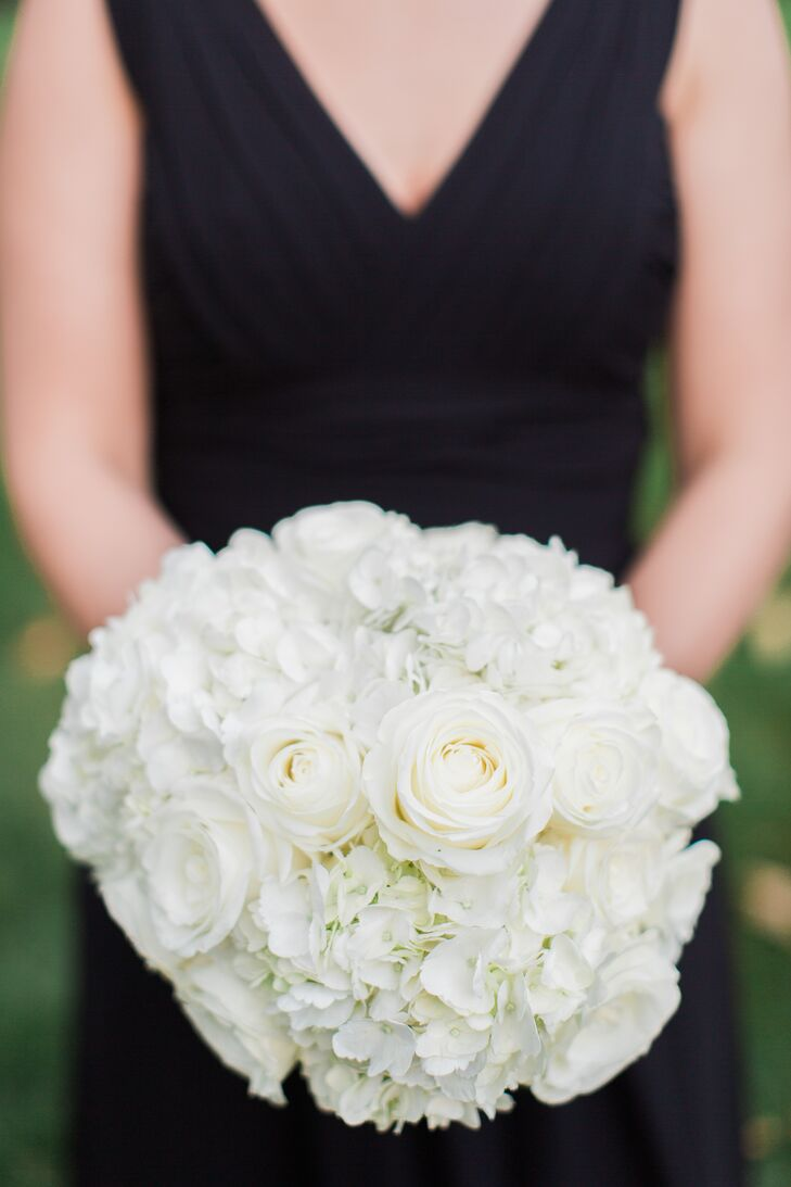 Adding some contrast to their all-black looks, each bridesmaid carried a classic bouquet from Karma Floral and Event Design. The pros filled each one with white roses between bunches of hydrangeas. Its thin wrap made the arrangements look even more organic.