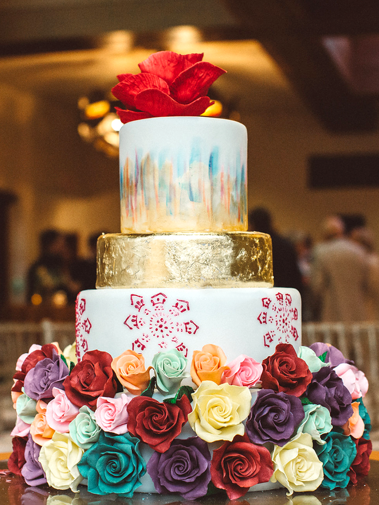 Multicolor rose decorated wedding cake with watercolor designs and gold foil