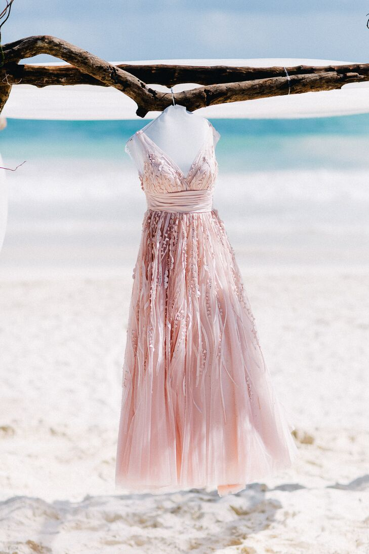 Danielle wore an incredible blush wedding dress with a low V-neck and sequin accents trailing down the flowy, ethereal skirt. The Watters Soledad dress matched the wedding's romantic, beachy vibe.