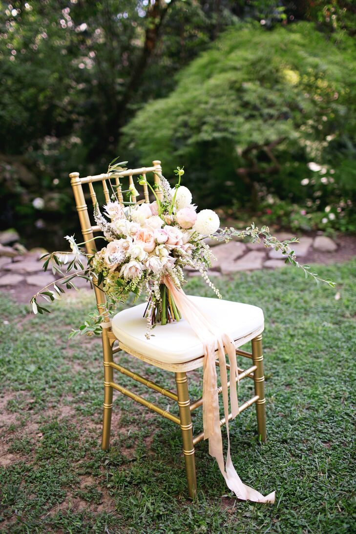 The neutral-colored bridal bouquet was filled with a variety of flowers accented with greenery, many of which were roses, and the arrangement sat upright on a gold chiavari chair.
