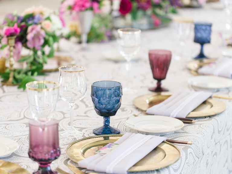 Colorful glassware in burgundy and blue with gold chargers on a lace tablecloth at a wedding reception
