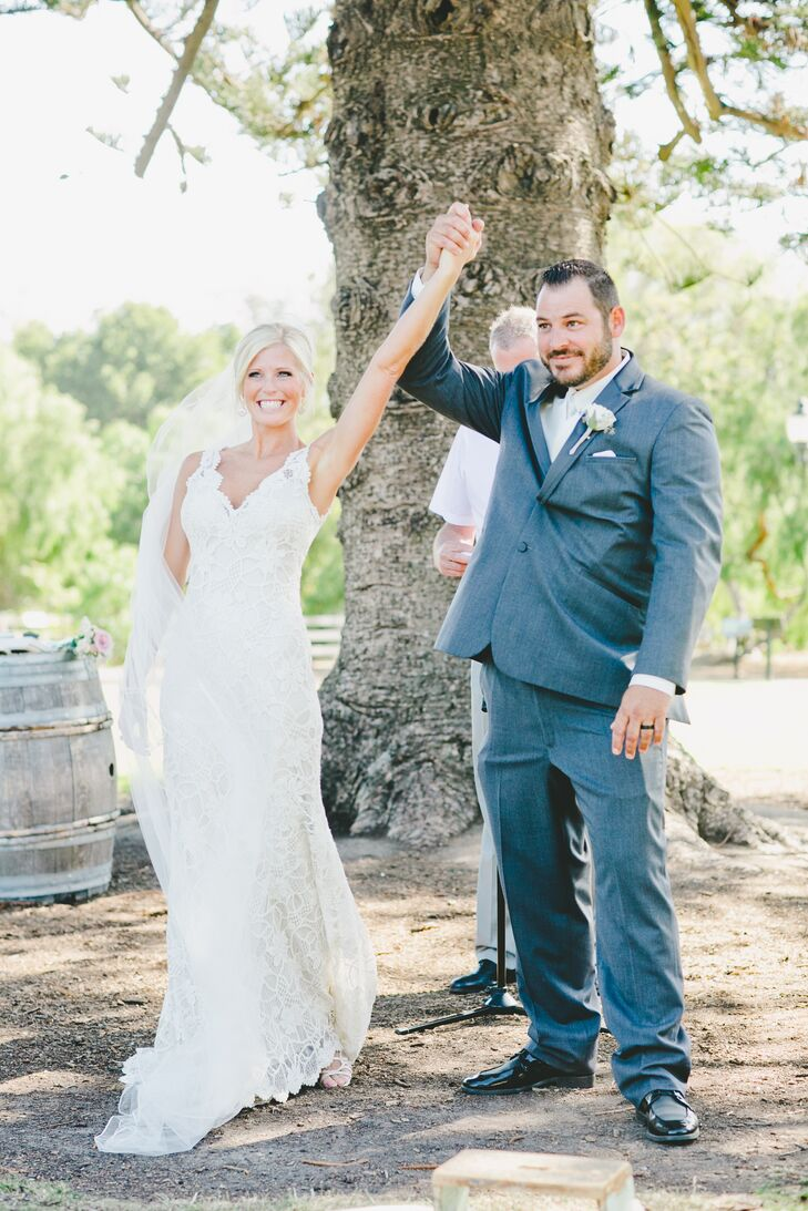 Victoria and Robert lifted their hands in celebration after their first kiss at the outdoor ceremony at Camarillo Ranch in Camarillo, California. Robert had a single ivory rose pinned to the lapel of his charcoal gray jacket, which matched Victoria's soft-colored flower bouquet.