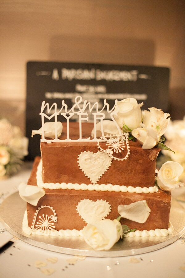 The square tiered wedding cake was decorated with white piping and white roses.