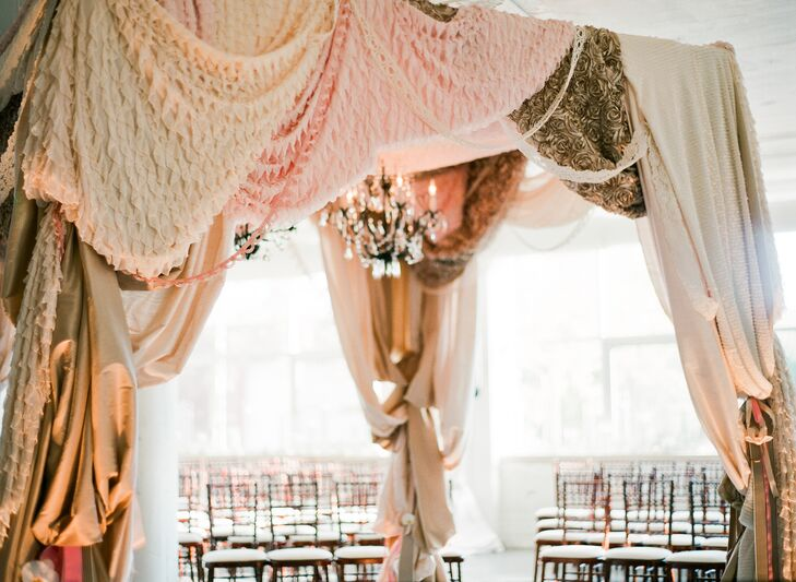 A stunning canopy of textured fabric panels in varying blush hues stood at the center of the room, a crystal chandelier hanging from its center where it cast a warm ambient light over the couple as they exchanged vows.