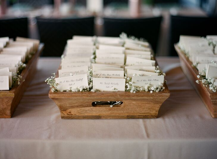 The escort cards were printed on ivory paper with mint borders and black calligraphy in a typeface called asterism. Andrea loved how whimsical and romantic the font was. For a little rustic flair, the cards were displayed in a bed of baby's breath in vintage wooden boxes, which helped set the tone for the gorgeous shabby chic reception.