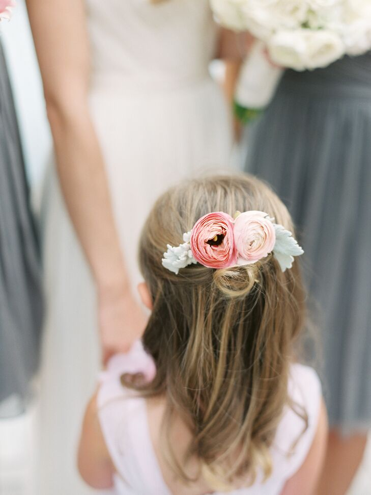 The flower girl's hair was pinned in a half-up hairstyle with a blush and pink floral hair accessory.