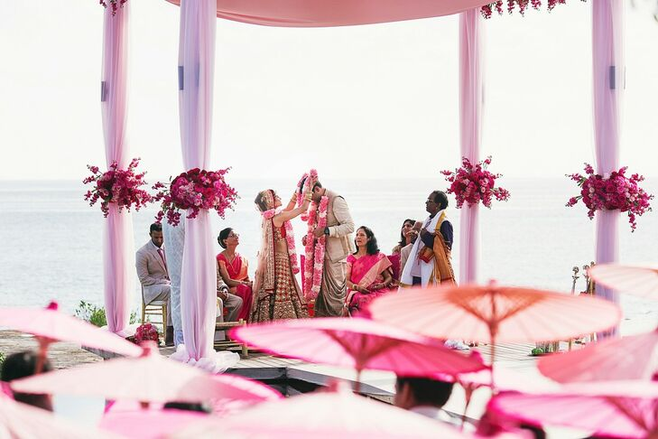 Melanie and Neeraj exchange garlands, a key component of the traditional South Indian ceremony. The garlands represent their consent to be married to each other. The ceremony took place under a draped mandap of blush fabrics.