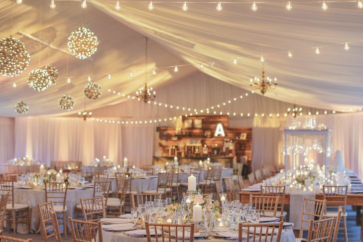 "The reception tent at Hamilton Farm Golf Club in Gladstone, New Jersey, was illuminated with crisscrossing rows of string lights, grapevine balls and chandeliers. A handful of candles at each table added a soft glow throughout. ""Lighting was huge for us: the string lights, grapevine balls and incredible head table installation,"" Kellye said."