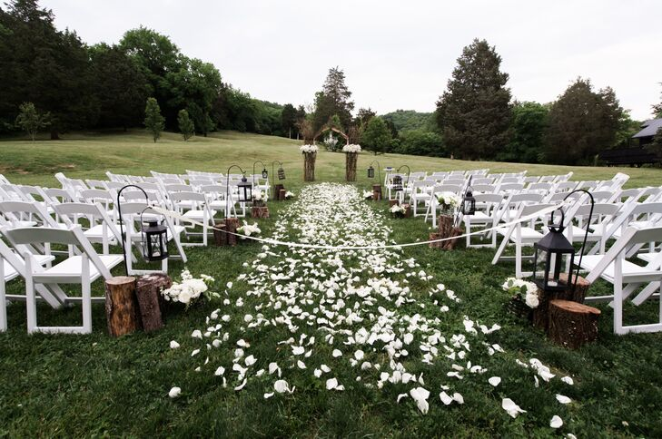 The meadow ceremony aisle was decorated with a mix of tree stumps, lanterns and floral arrangements in galvanized pails.