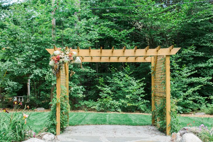 "Chrissy and Mike created an outdoor oasis for their ceremony. The pair planted a vibrant daylily garden at their camp and designed a stone aisle leading to a quaint wooden arbor covered in lush vines, under which they would say their ""I dos."" On the day of the wedding, Cymbidium Floral decorated the arbor with a beautiful, cascading arrangement of dahlias, roses and hydrangeas."