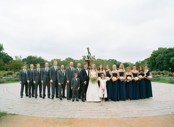 """I wanted my bridesmaids' style to be reflective of my own,"" says Katie. The bridesmaids wore floor-length navy dresses with white anemone bouquets and custom-made statement necklaces in colors to match the bride. The groom wore a trendy navy tuxedo with a polka dotted bow tie, and the groomsmen wore tuxedos in charcoal gray with matching polka dotted ties."
