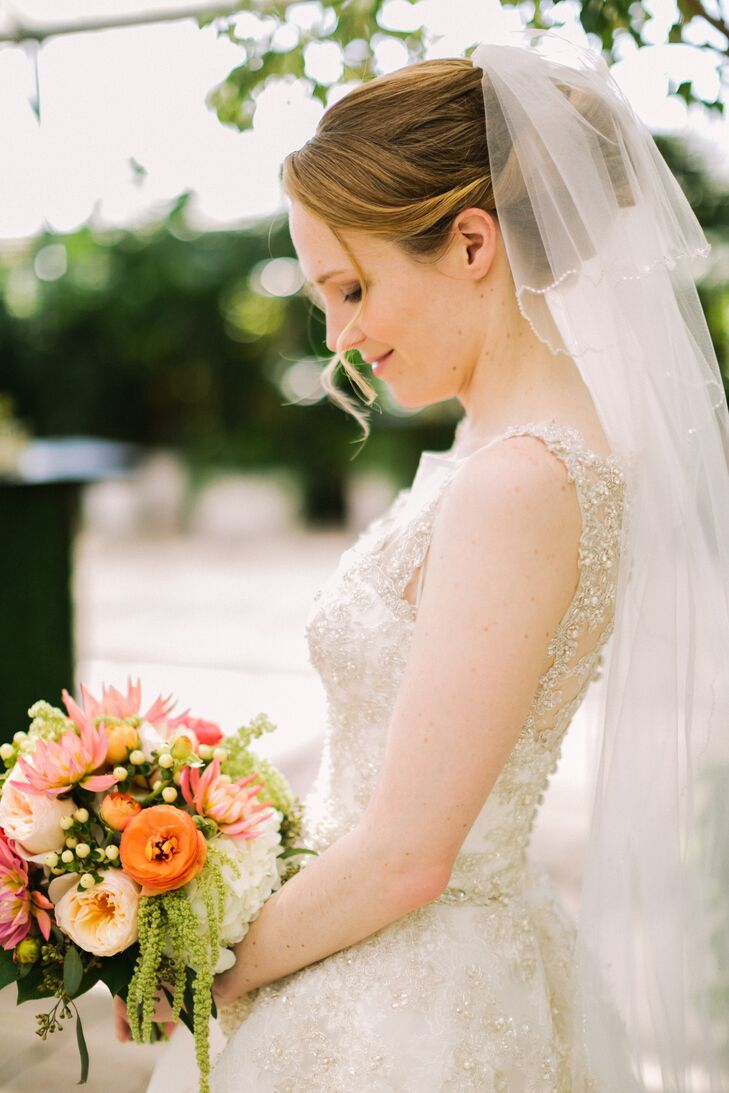 Sarah carried a 12-inch custom bouquet wrapped in an ivory satin ribbon, consisting of coral, peach and ivory dahlias, garden roses, ranunculus, mums, hydrangeas, hypericum, eucalyptus and hanging amaranthus.