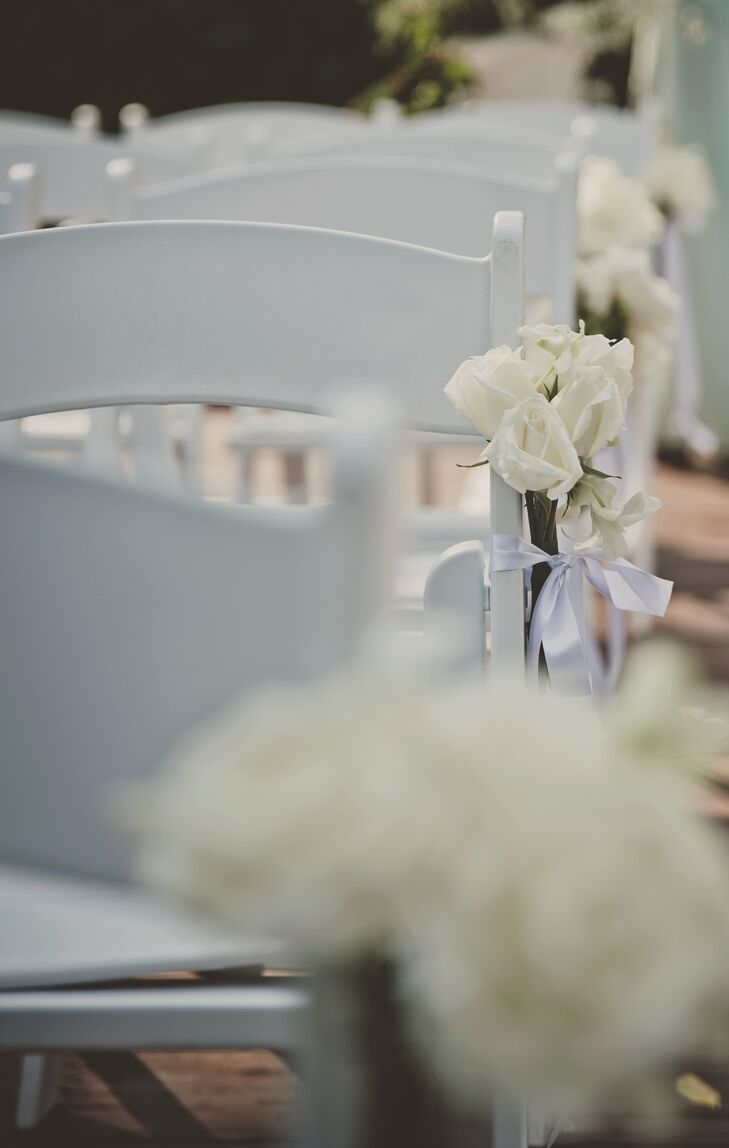 The aisle was lined with small white rose bouquets that hung from the white chairs adding a touch of sophistication to the ceremony.