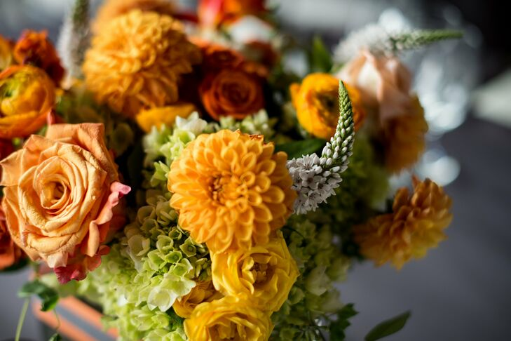 Orange dahlias were paired with ranunculus, veronica and roses to create a lush, fall-inspired bouquet by Jen House Design.