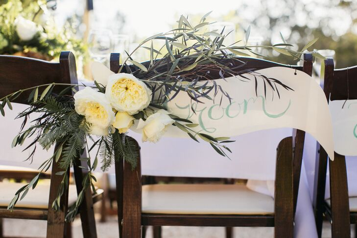 One of the bride's cousins created the bride-and-groom pennant flag signage on the back of the couple's reception chairs. Ranunculus with sprigs of natural ferns sprouted around the signs to add to the organic atmosphere.