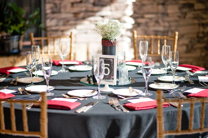 Black tablecloths dressed the dining tables at the reception, with red napkins and white dinnerware organized on top. The black and white framed table number was in front of the baby's breath centerpiece.