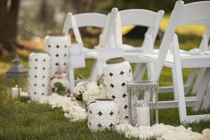 The aisle was decorated with white and gray lanterns, pillar candles and soft, cream and pink colored flowers.