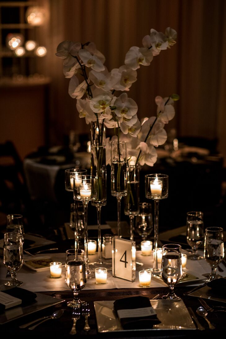 The candlelit reception tables were decorated with white orchid centerpieces.