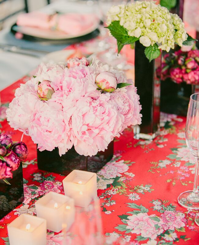Pink peonies in a cleanly solid black glass cube vase stands out nicely against the patterned tablecloth