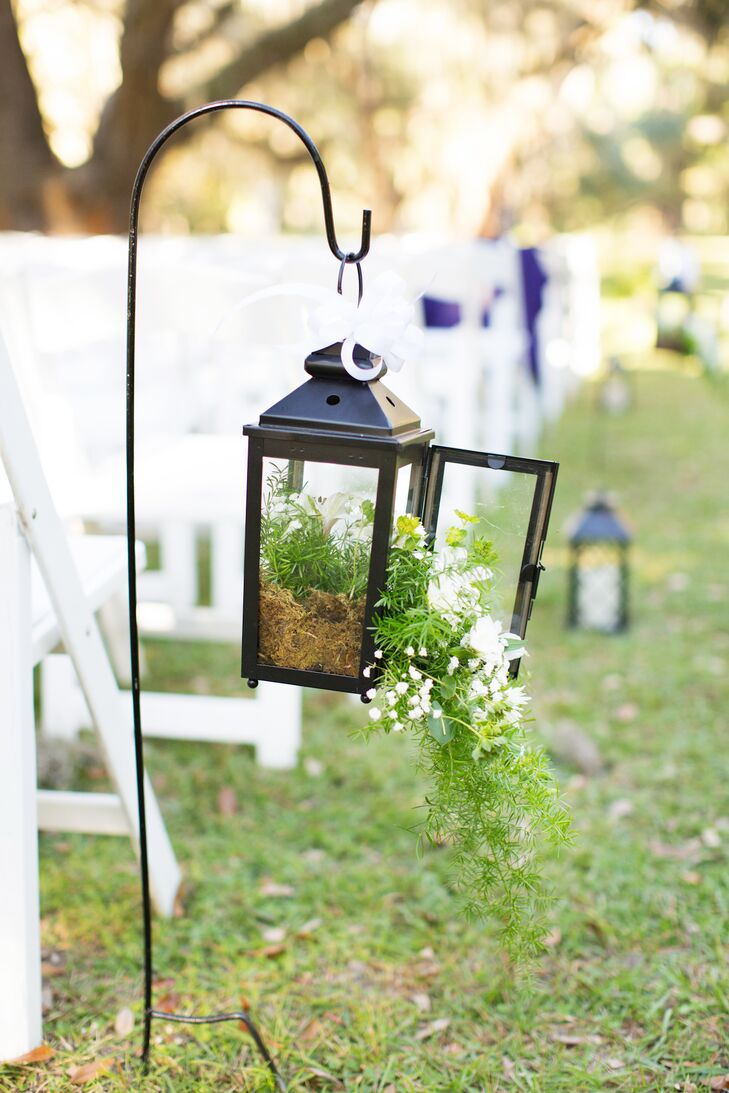 The ceremony aisle was lined with black lanterns hanging from shepherd hooks. It was filled with lush greenery and simple white flowers.