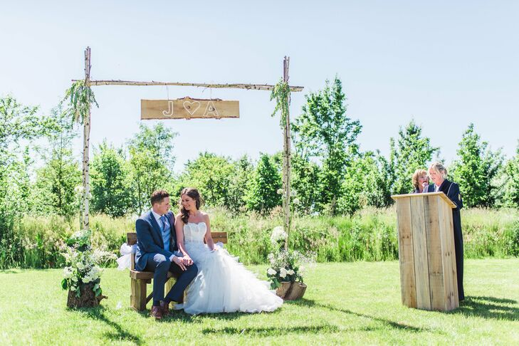During the ceremony, Amanda and Jan sat on a wooden bench out of an arch made of birch wood. The arch was decorated with greenery and featured a sign with the couple's initials.