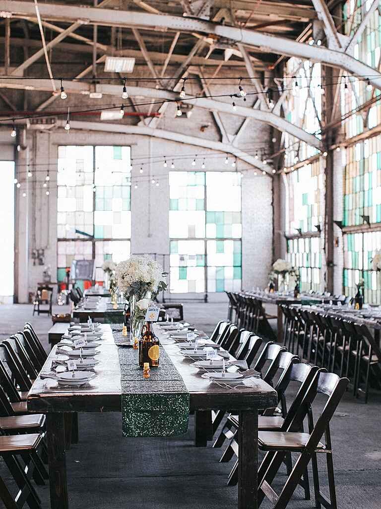 Industrial wedding venue with sequin table runners and bistro lighting