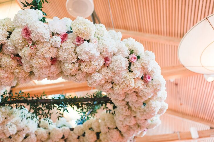 A giant floral wreath suspended above the dance floor was the focal point of the reception at Rosine Hall at the Dallas Arboretum in Dallas, Texas. It had a mix of white hydrangeas with fluffy, textured peonies and pink spray roses.