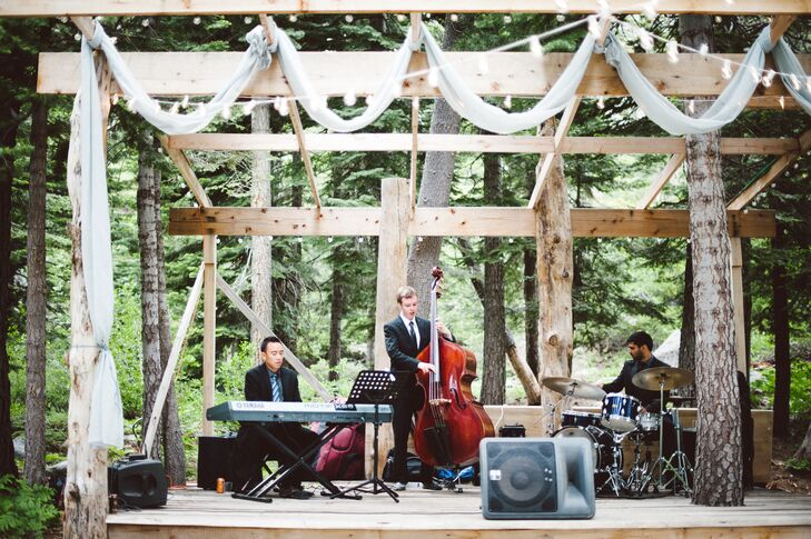 A live band played music on top of a wooden stage draped with white linens and string lights throughout the wedding day. Since Kimberly and Derek are both musicians, they put a lot of thought and planning into the music selections.