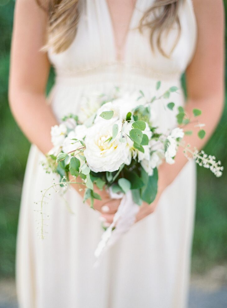 Bridesmaids donned long, flowing halter dresses and carried bouquets of garden roses with pops of greenery.