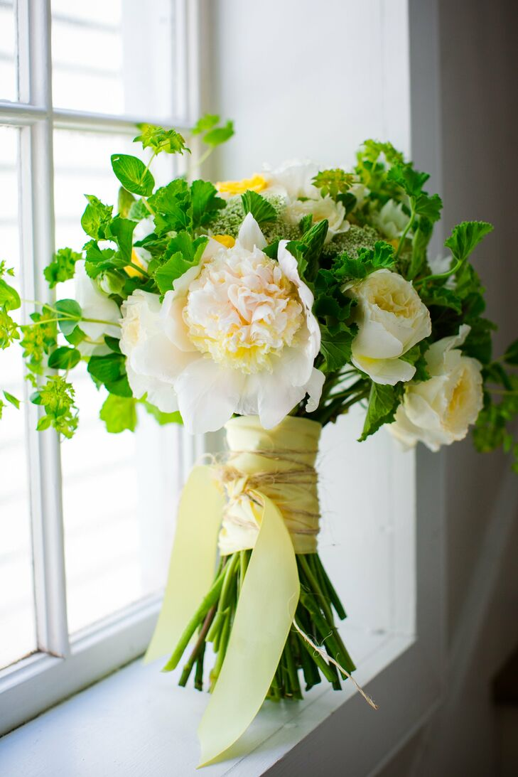 """I loved our flowers,"" Carly says. ""Blue Planet Green Events completely exceeded our expectations."" Carly carried a bouquet of roses and peonies with soft yellow accents and greenery."