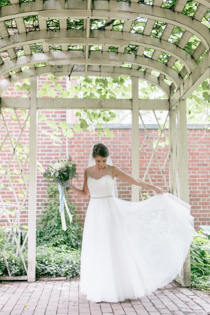 Jen's Penelope by Watters A-line gown with illusion neckline was the first one she tried on, the epitome of romance and comfort. The skirt, featuring soft netting, was accented with a crystal sash at the waist. The bodice featured delicate hand-placed lace motifs.