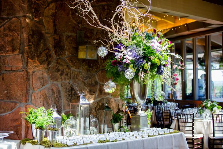 Hand-lettered escort cards were displayed atop a bed of moss dotted with silvery lanterns and an ornate arrangement of bright purple blooms, textured greenery and manzanita branches to create a whimsical display.
