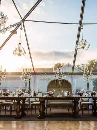 Chandeliers hanging over reception tables for a rustic wedding