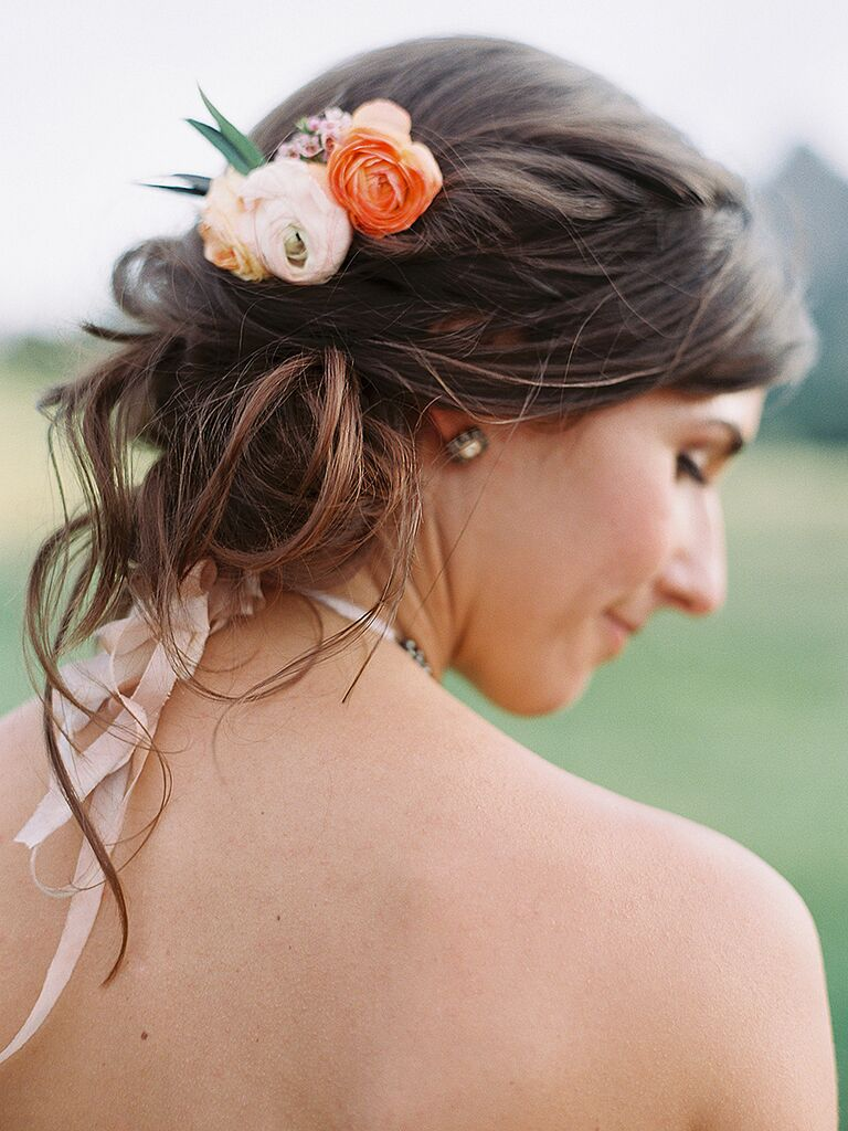 Messy bridesmaid hairstyle with a low chignon and ranunculus