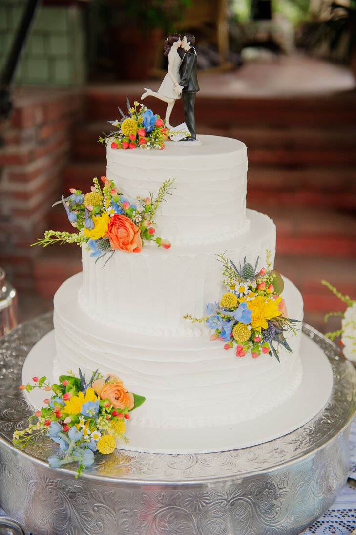The three-tier white wedding cake had accents of colorful blooms used throughout the day. The classic dessert had a topper depicting a bride and a groom, fitting the occasion perfectly.