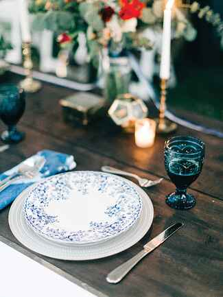 Blue and white place settings and colored glassware for unique reception decor
