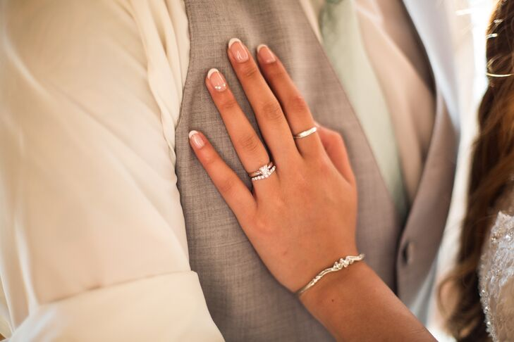 Denise rested her hand on James's gray vest, with beautifully manicured nails done for the wedding day. She wore a beautiful silver bracelet that complemented the collection of her elegant wedding rings.
