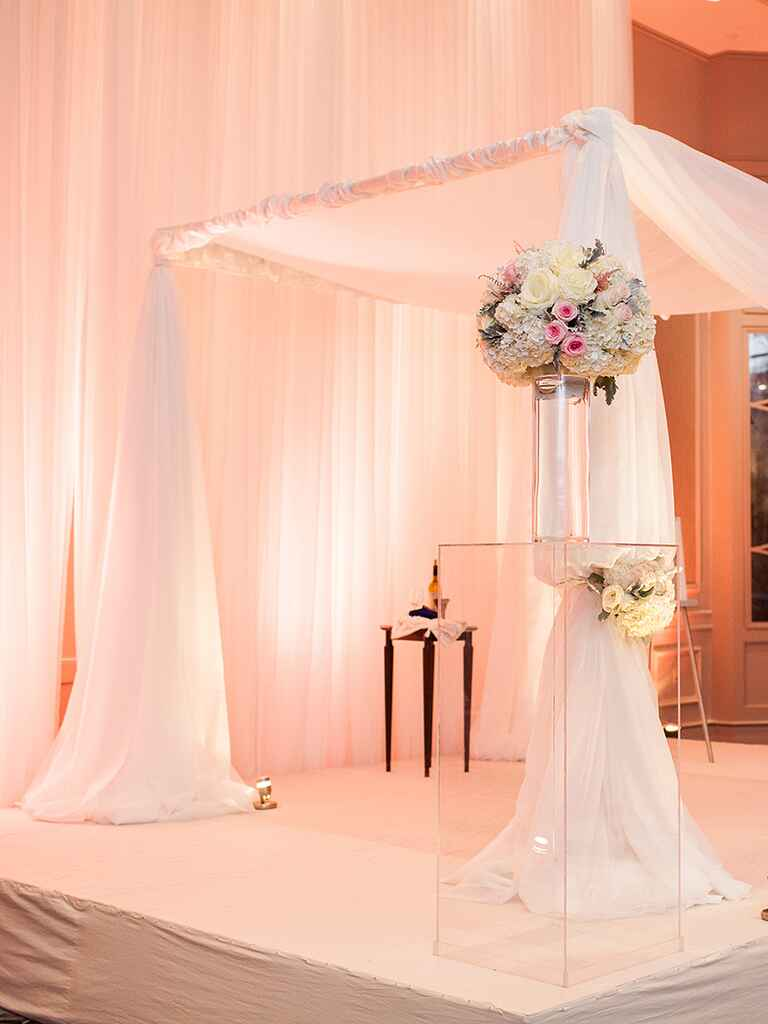 A dreamy chuppah with sheer white fabric draping and blush bloom accents
