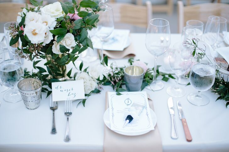 At each dining table setting, simple white dinnerware was paired with champagne-colored linens. The plates were covered with white stationery that had wine-stopper wedding favors on top. Guests found their seats marked with a simple black-and-white escort card.