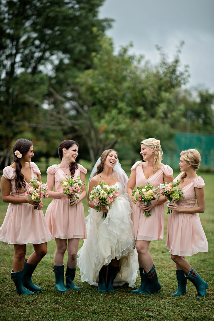 Noelle found matching peach pink cap-sleeve chiffon dresses by Minuet online at Lulus for her bridesmaids to wear. They accessorized with coordinating side ponytails, pink floral hair accessories, and green rain boots for the rainy ceremony.